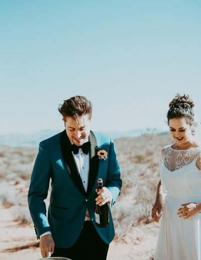 Claire married her sweetheart in the Las Vegas desert.  Claire wore a gorgeous PS With Love bespoke hair vine in rose gold, agate gemstones, rose gold beaded leaves, delicate vine tendrils and intricately handmade and painted teal forget me nots. image https://jamiey.com